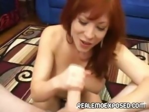 Busty redheaded MILF strips, gives a POV titjob then strokes it good