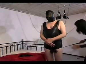 Attractive dominatrix in latex gets on bed and starts whipping her slave
