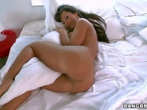 Curvy dark haired MILF Lisa Ann is naked in bed.
