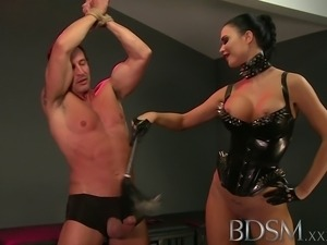 Slave boy in metal stocks as he receives anal attention from his Mistress