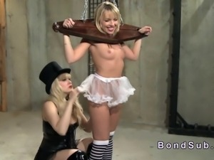 Blonde sub in wooden shackles gets breasts caned