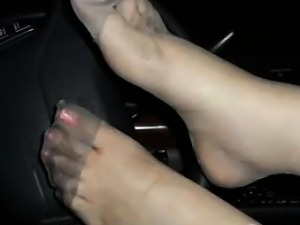 Her Nylon Covered Feet Close Up In The Car