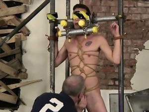 The boy is restrained in a cage of metal and blindfolded
