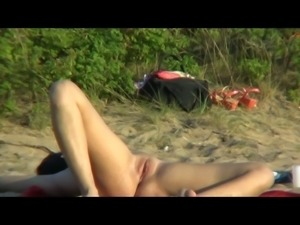 Girl lying with her legs spread shows all her pussy on beach