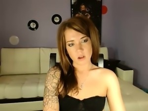Tattooed redhead fingers her clit and gets dressed to watch