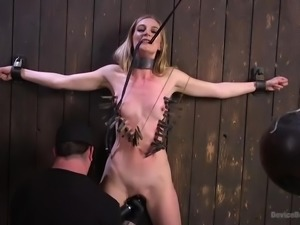 Mona is tied to the wall and she has clothespins attached to her, courtesy of...