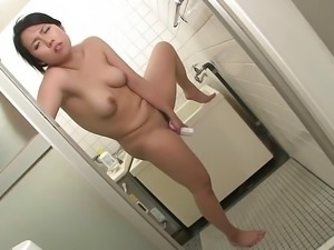 Horny brunette masturbates in the kitchen with a dildo
